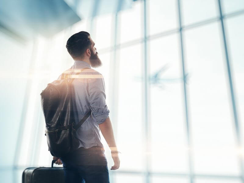 Bearded man standing at the airport with a suitcase