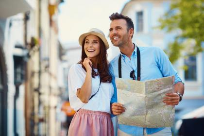 Happy couple with map visiting city