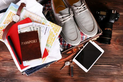 Packed suitcase of vacation items on wooden table, top view