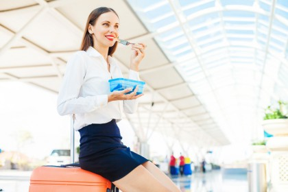 woman eating homemade food from plastic container while travelin